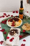 Table with food, bottle of champagne and glasses, rose petals
